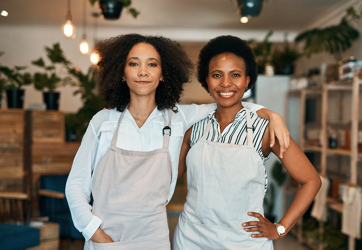 two women in aprons standing side-by-side, one with her arm over the other's shoulder