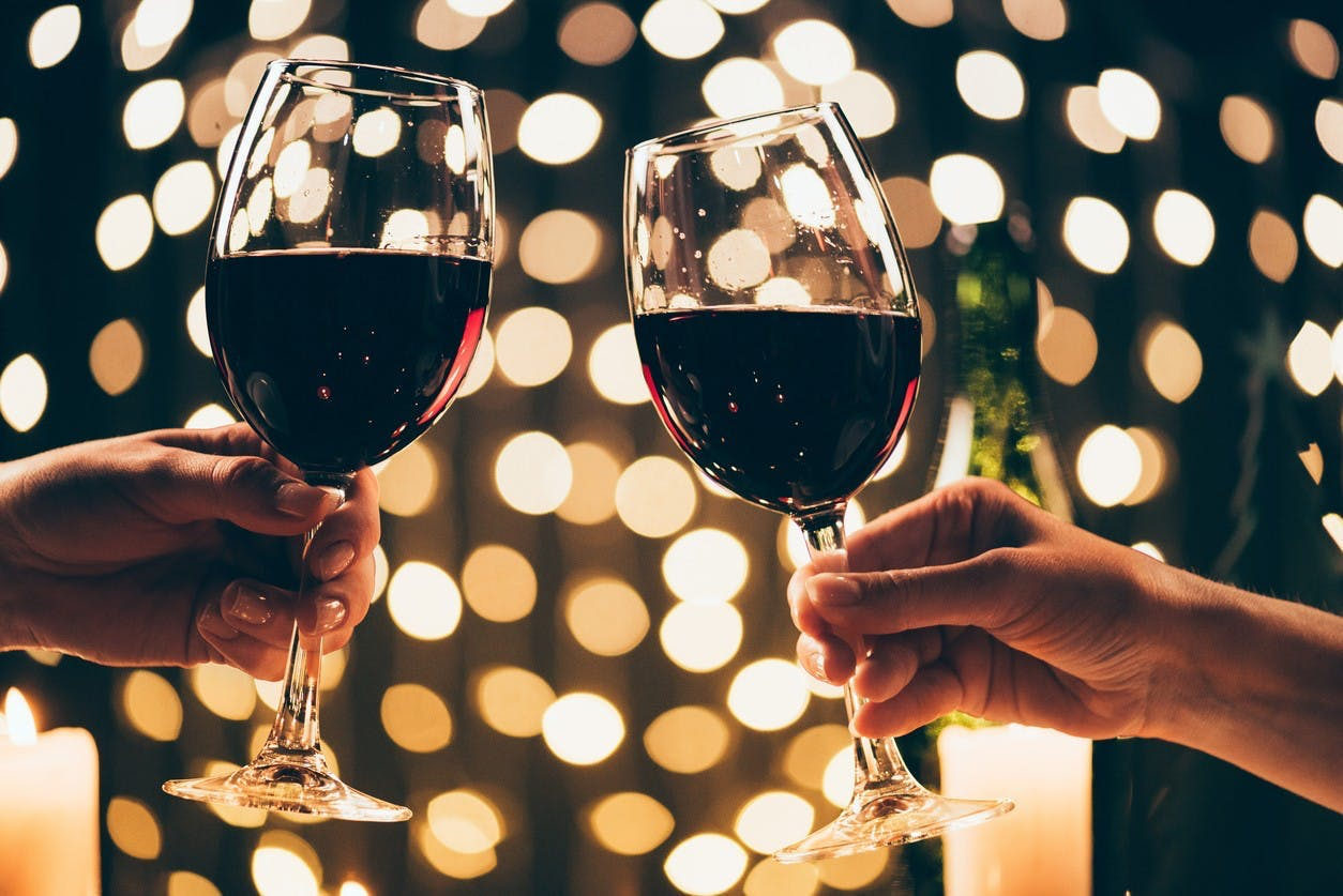 two people cheersing glasses of red wine
