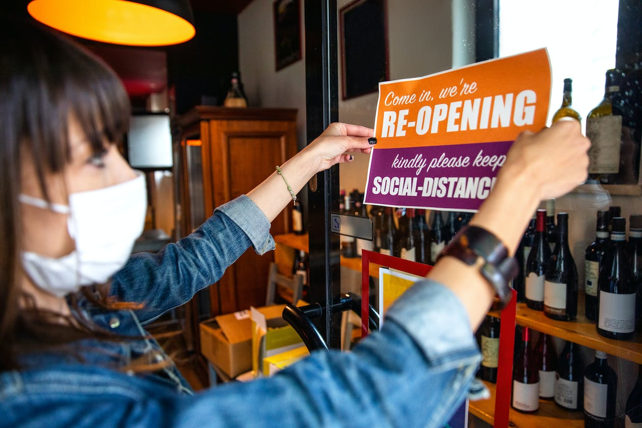 A restaurant owner puts up a reopening sign - COVID-19