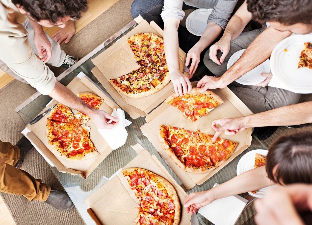 A group of people eating pizza together at home.