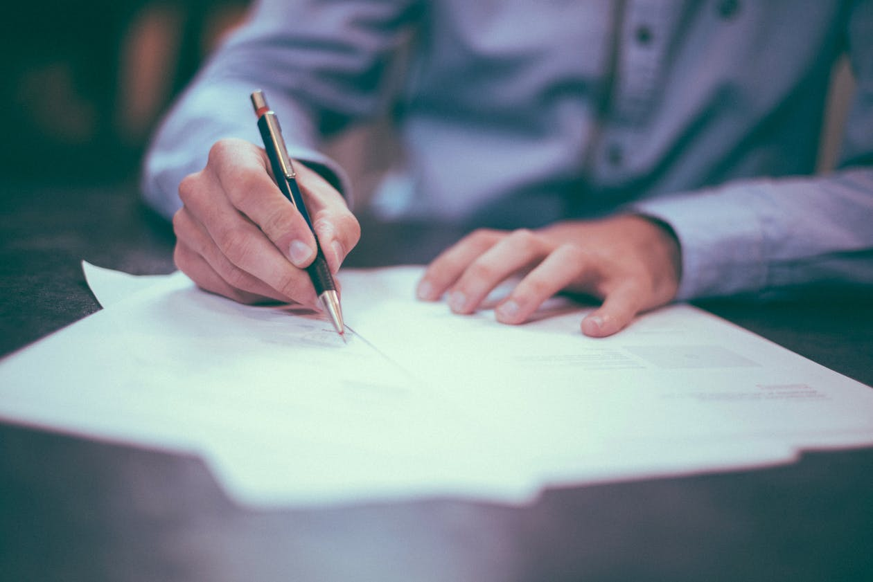 a person signing a contract.