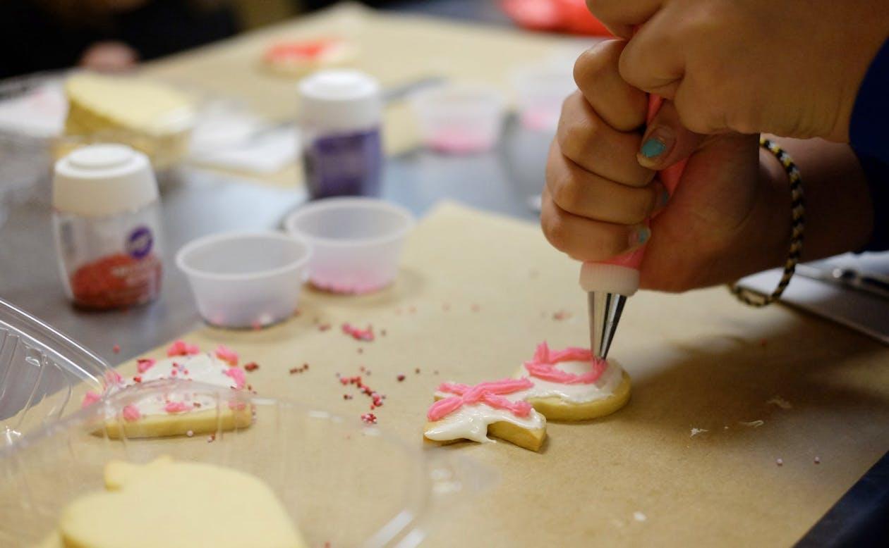 Young girl decorating cookies at Café Du Pain's class