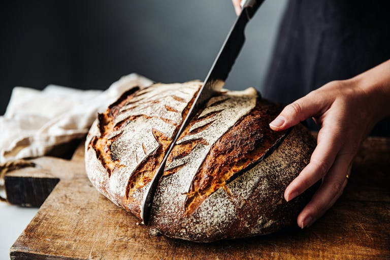 Baker cutting into a loaf of bread