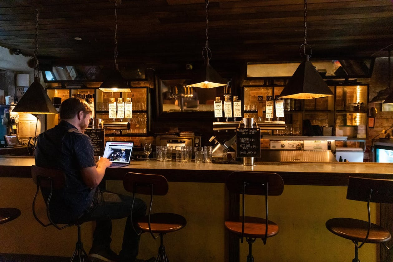 A man working on his laptop sitting at a wooden bar.