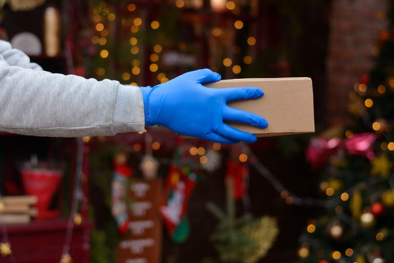 A person handing over a package during the holidays