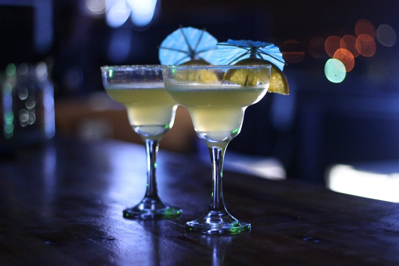 two glasses of margaritas sitting on top of a wooden table