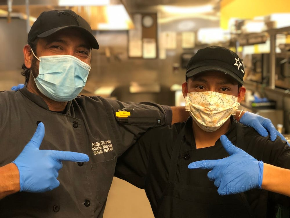 2 Kitchen Staff Wearing Masks Pointing at Each Other