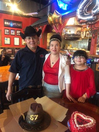 photo of a family in front of a table with cakes