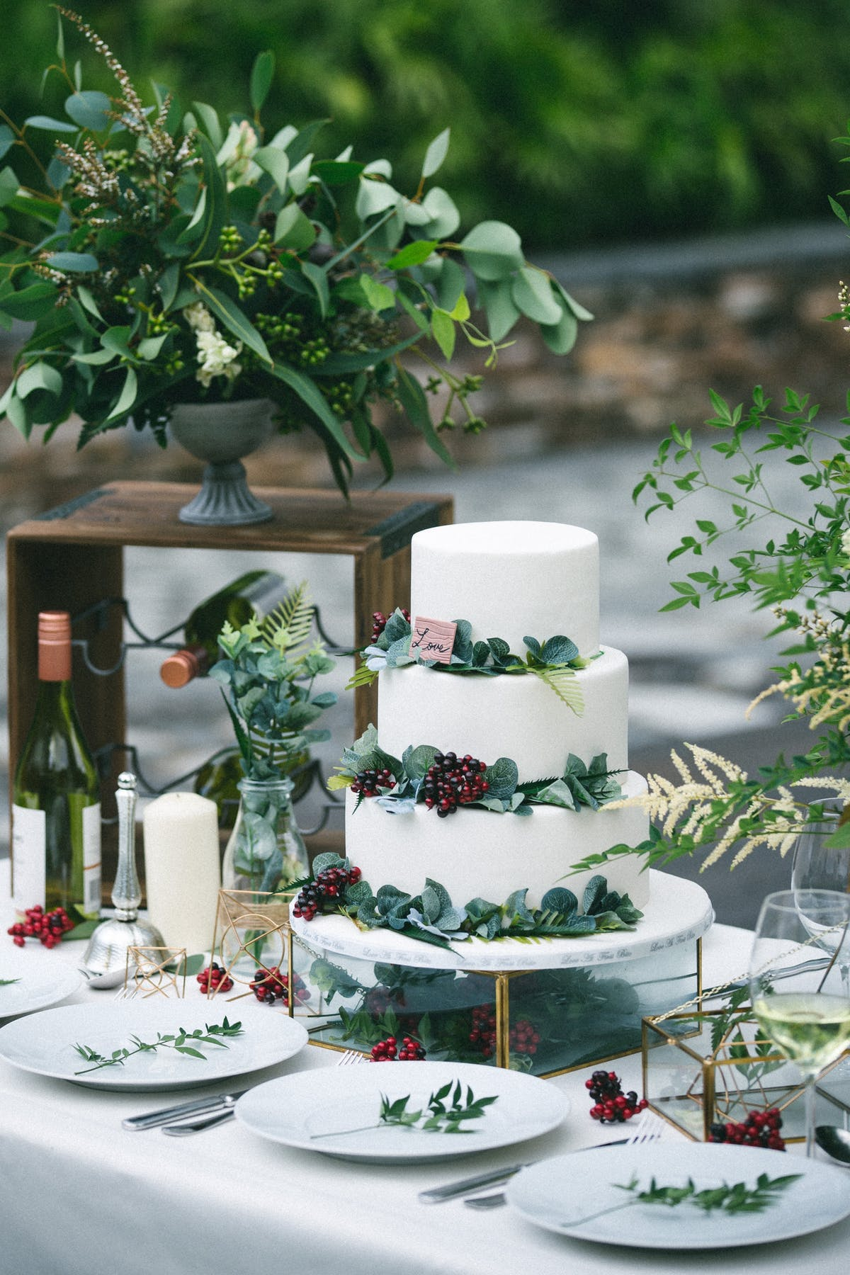 a vase of flowers on a table with a wedding cake