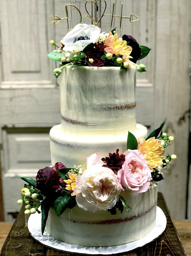 a bouquet of flowers in front of a wedding cake