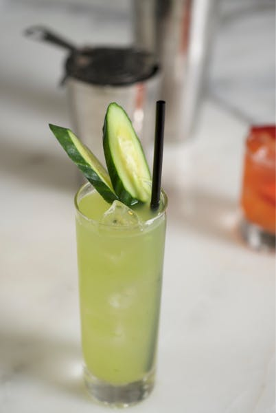 a green cocktail with cucumber