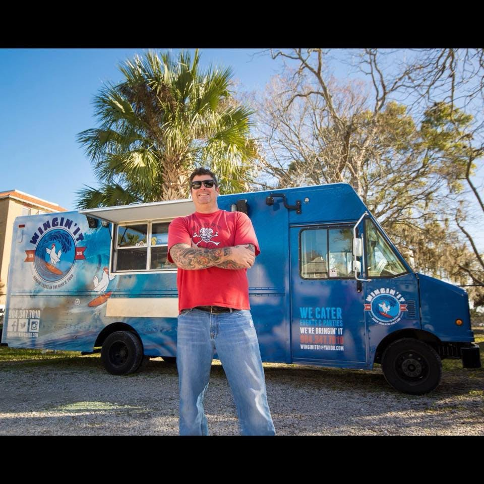 a person standing in front of a blue truck