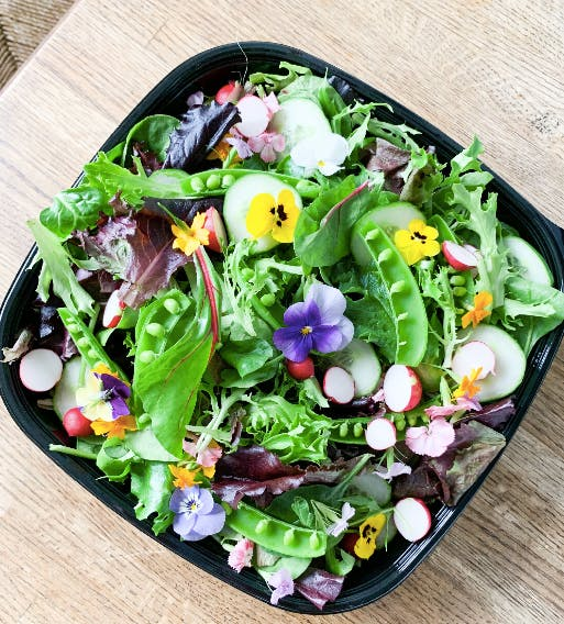 a salad sitting on top of a wooden table