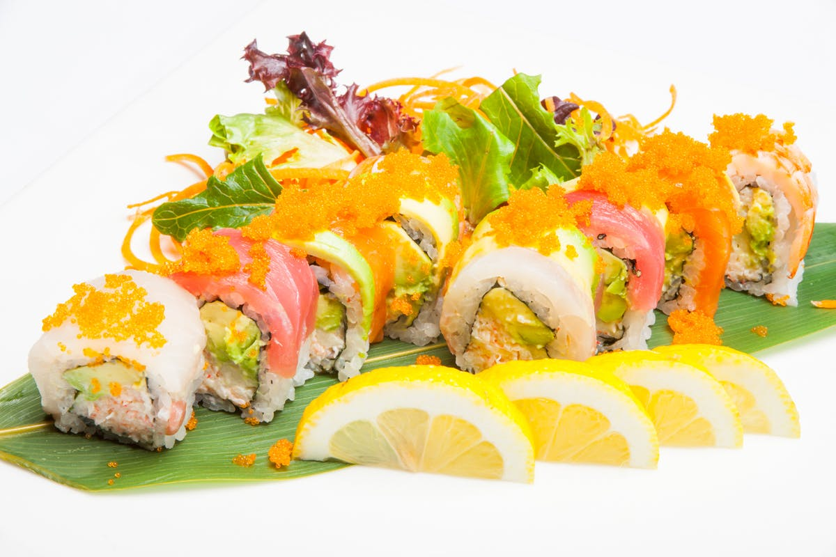 a plate of food with a slice of sushi