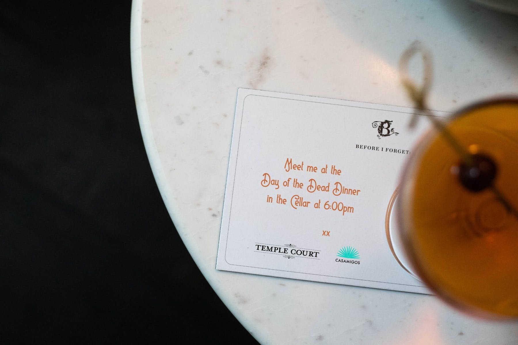 written invitation next to a cocktail