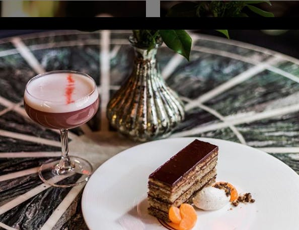 a piece of cake on a plate with a cocktail