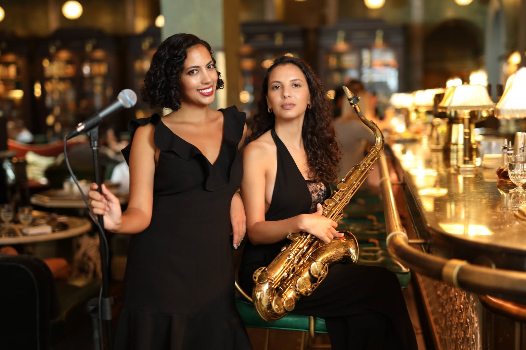 Two woman at the bar, one with a microphone, one with a Saxaphone