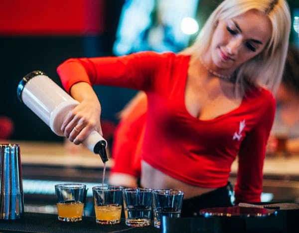a close up of a woman serving drinks on a table