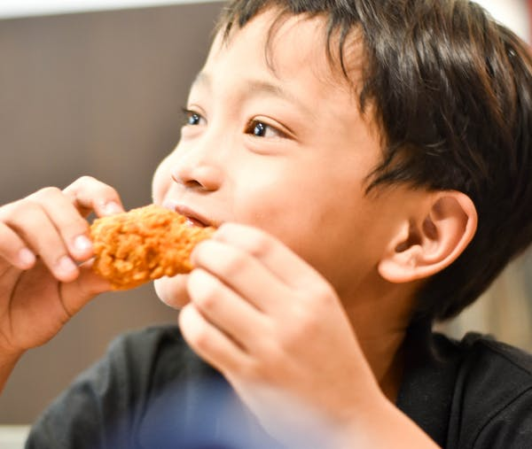 a young boy eating a slice of pizza