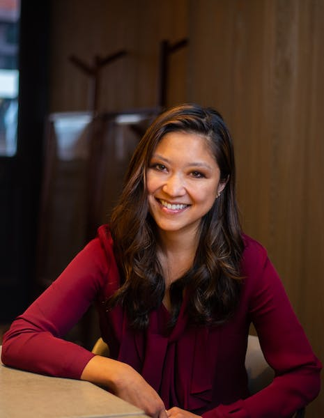 Emmeline Zhao sitting at a table with a laptop and smiling at the camera