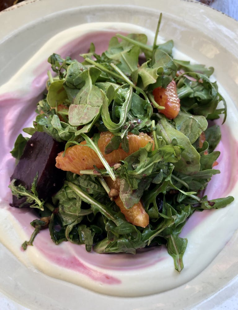 a plate of food with a green salad