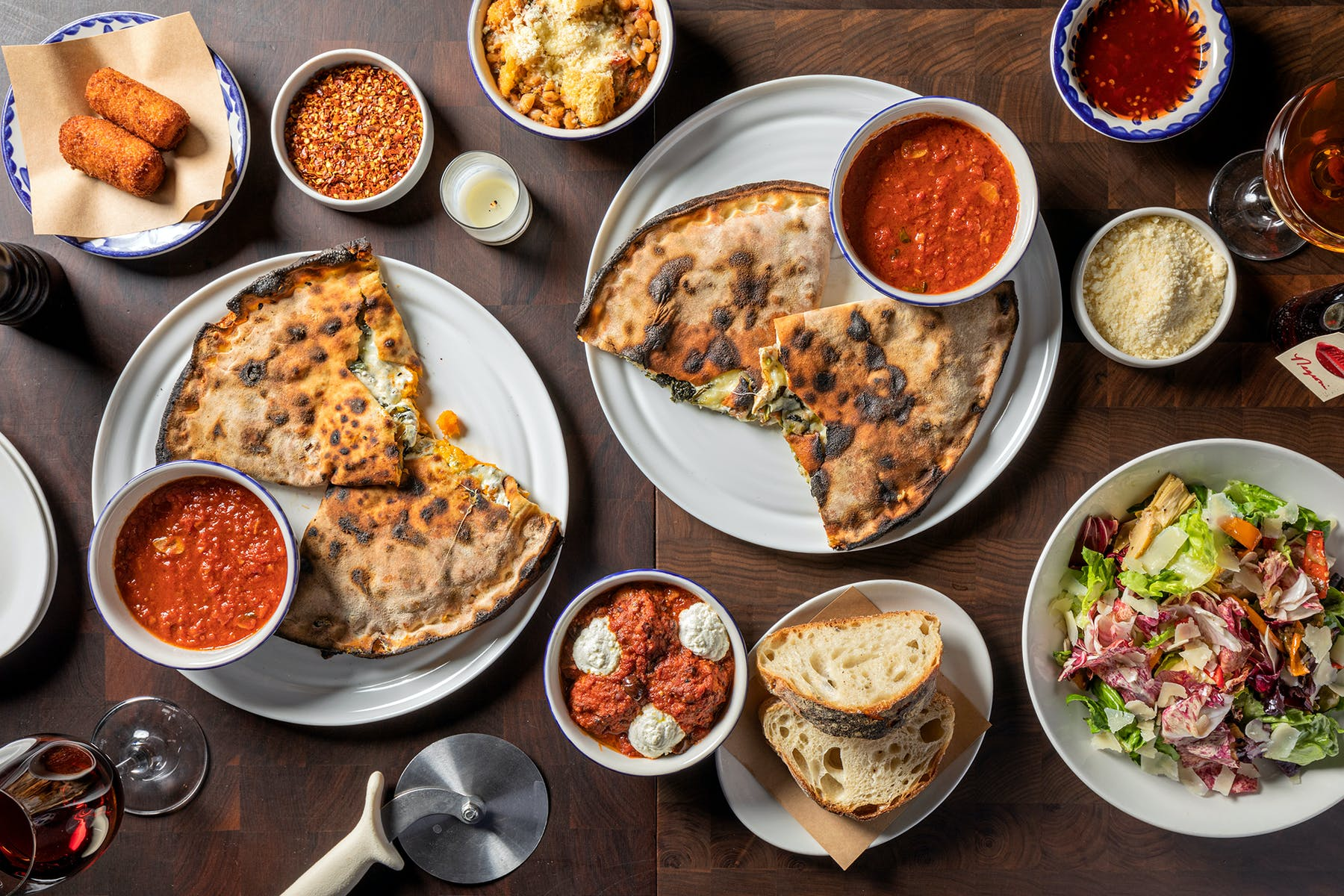 a table filled with calzones and sides from Marta