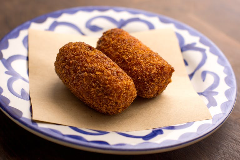 two tomato risotto croquettes on a plate