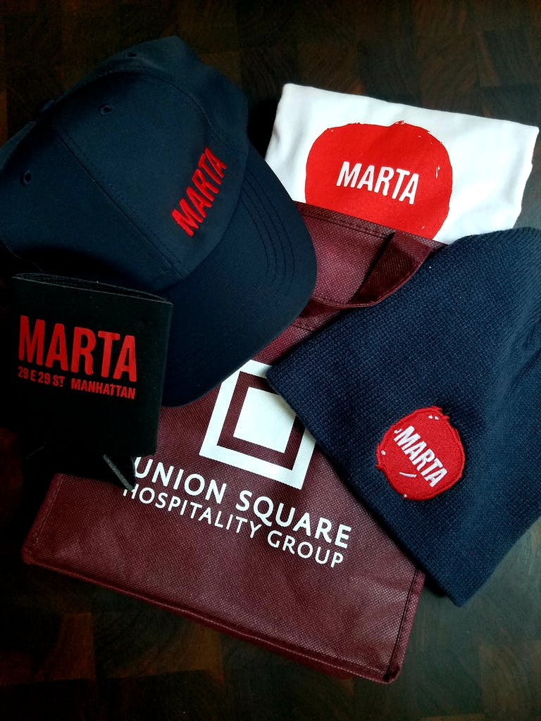 Marta hats and tshirts laid out on a table