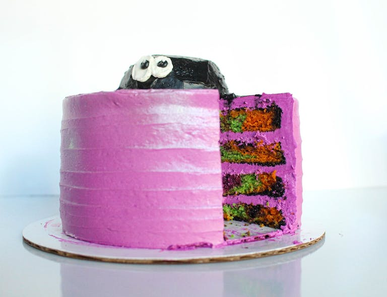 a pink cake sitting on top of a table