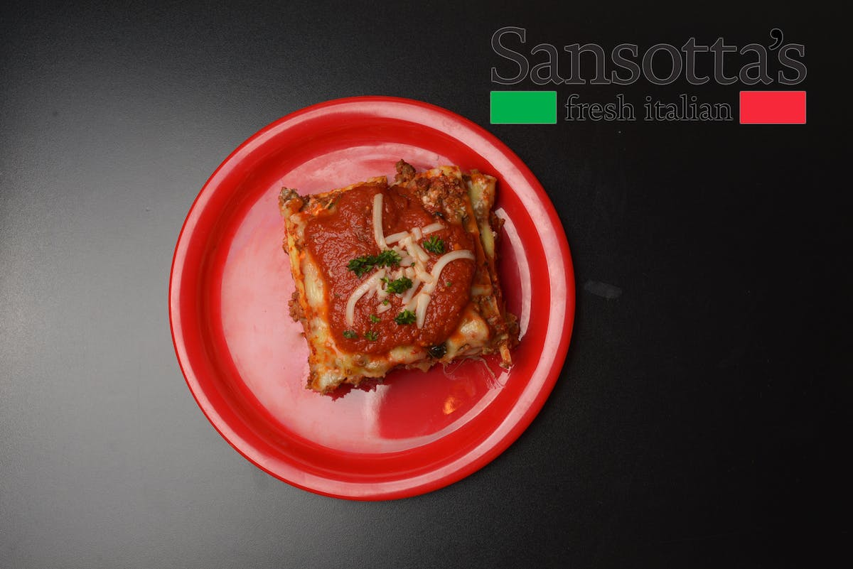 a red plate topped with a piece of lasagna