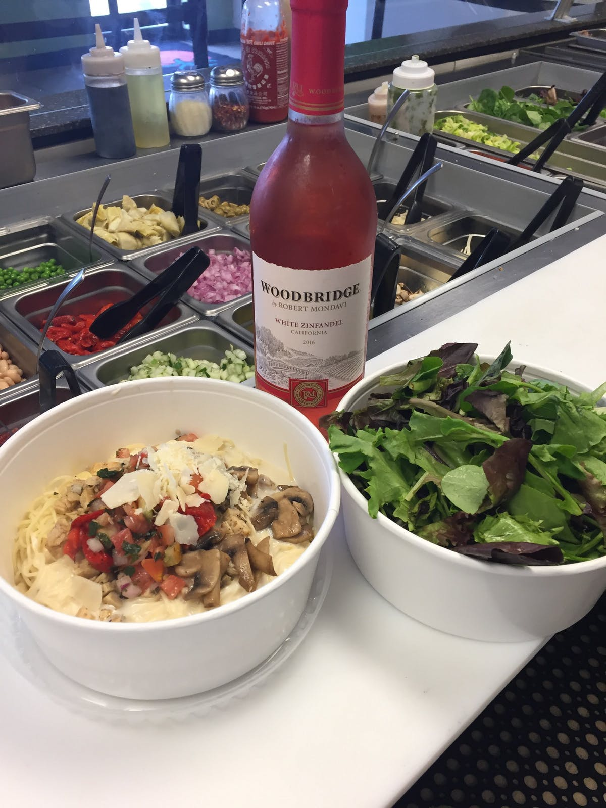 a bowl of salad and a bottle of wine