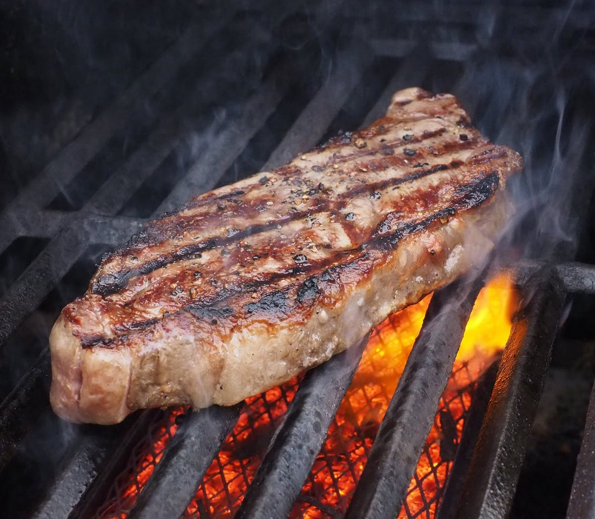 a piece of meat being cooked on a grill