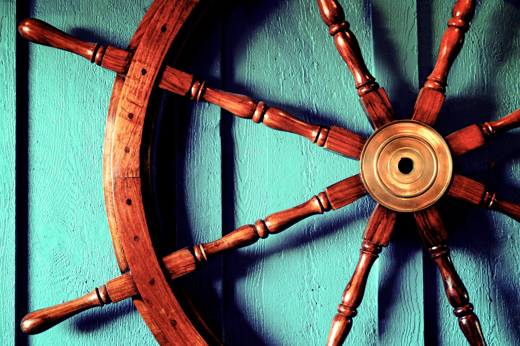 a closeup of a boat's wooden steering wheel