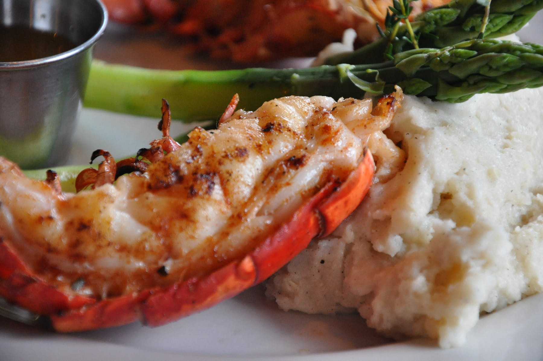 an cooked lobster sitting next to mashed potatoes