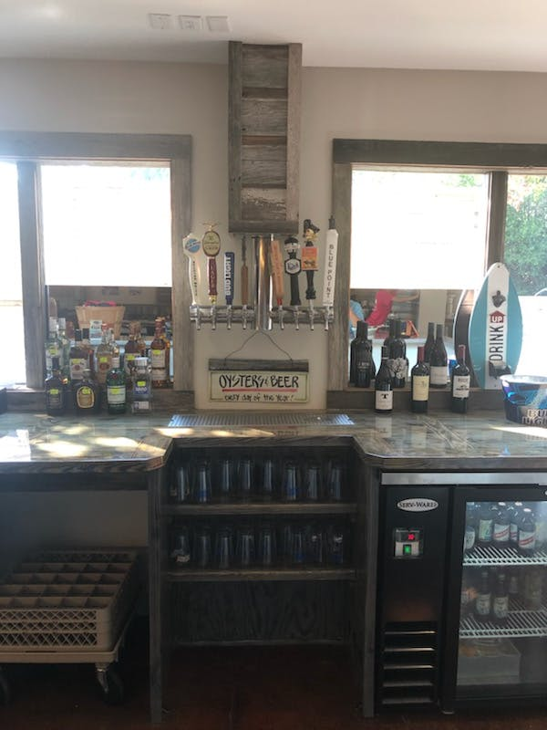 a bar topped with wine bottles and beers