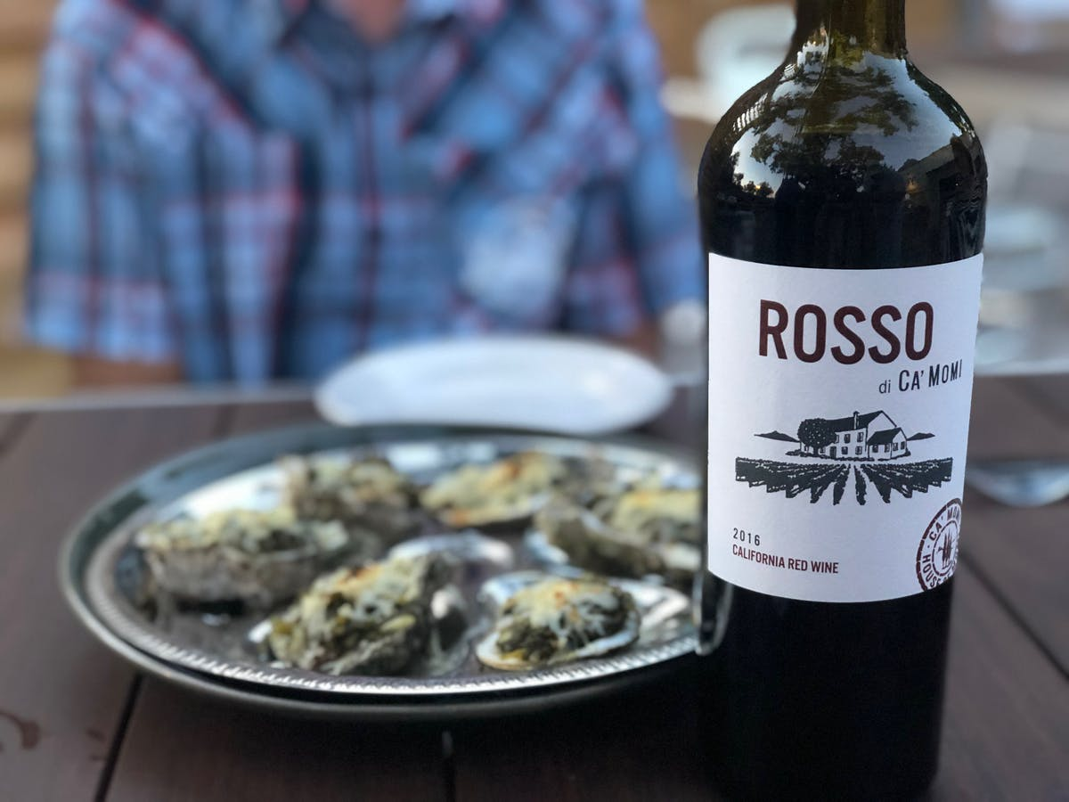 a plate topped with oysters sided by a wine bottle