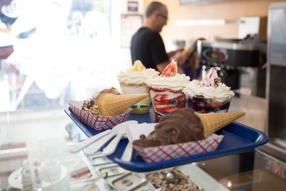 ice creams and sundaes sitting on a tray