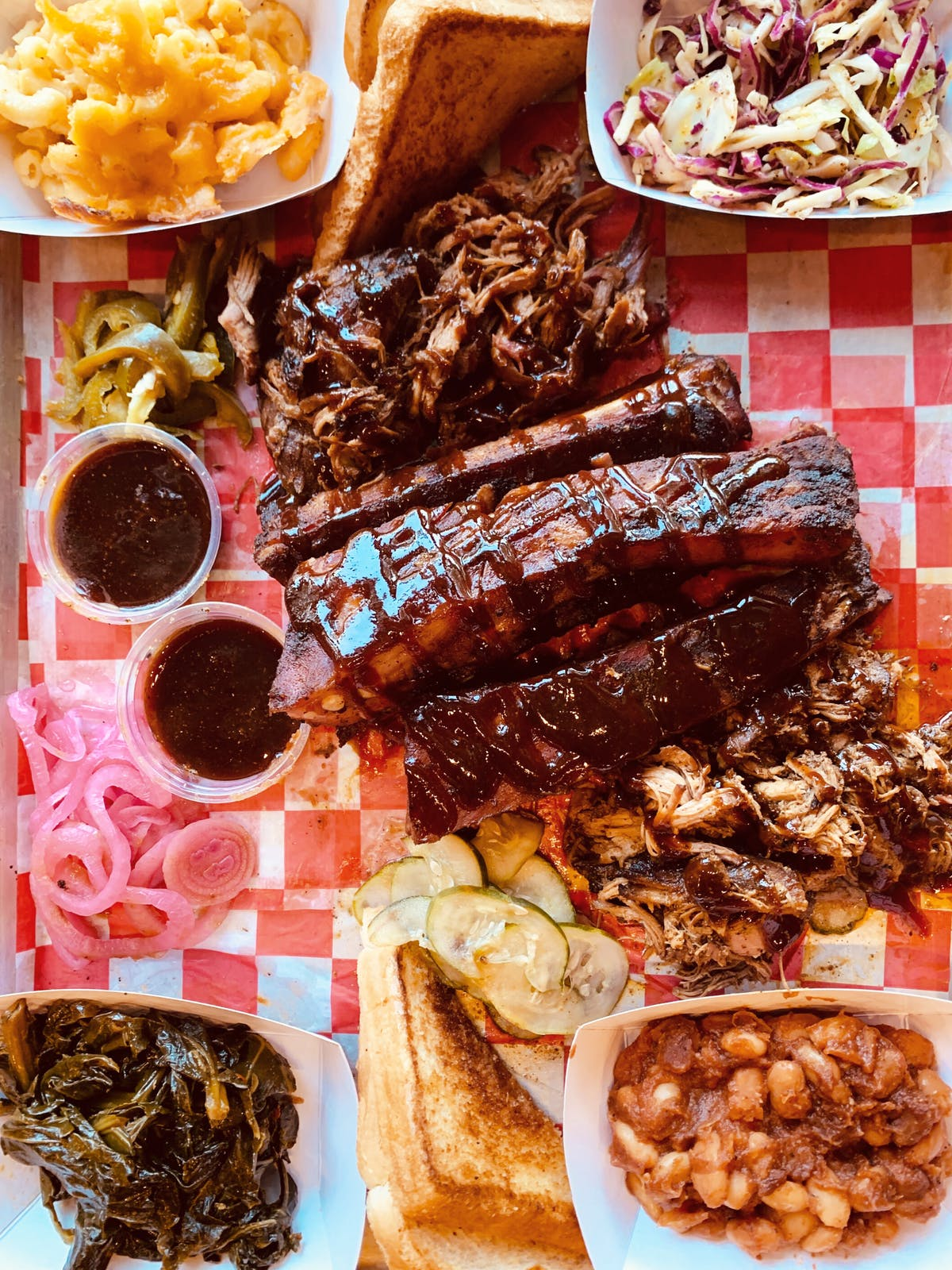 a tray with bbq meats, sauces, and sides