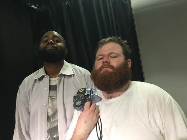 two men posing for the camera, one with a video game controller