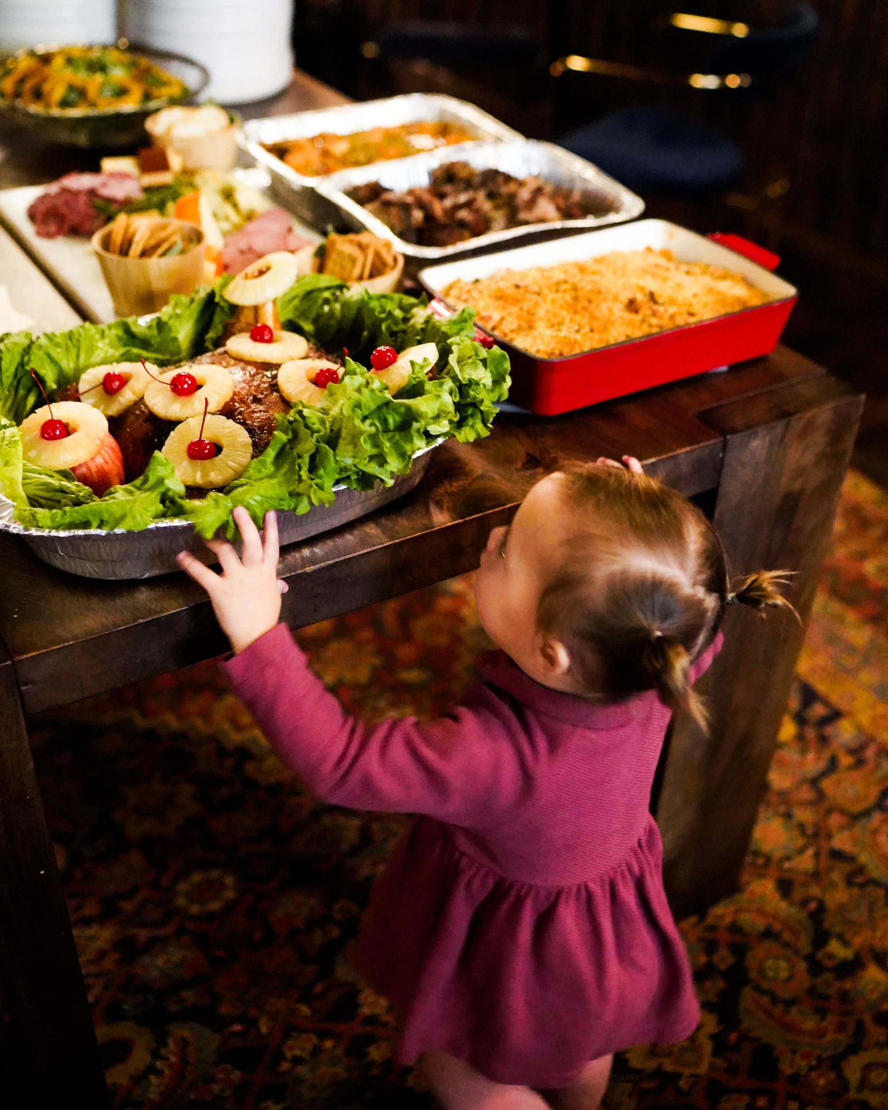 a little girl standing in front of a plate of food