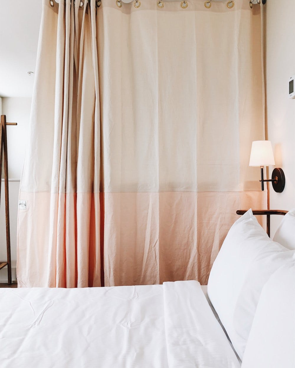 a bedroom with a bed and a curtain