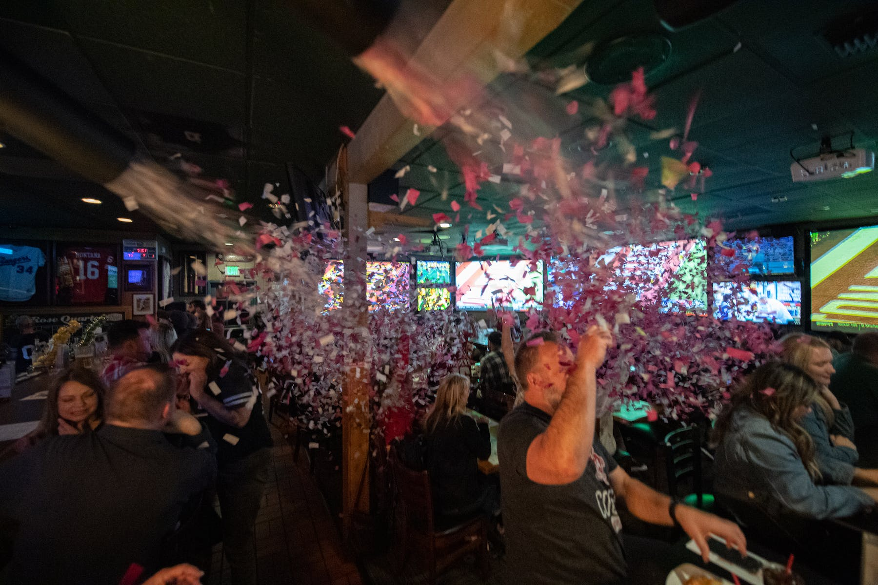 a group of people celebrating at the restaurant throwing confetti