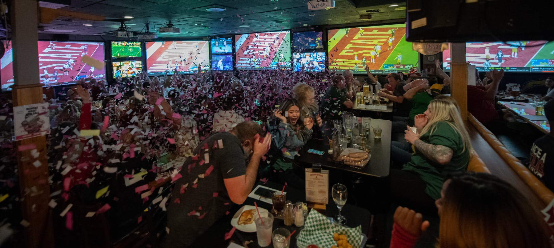a group of people at the restaurant celebrating and throwing confetti