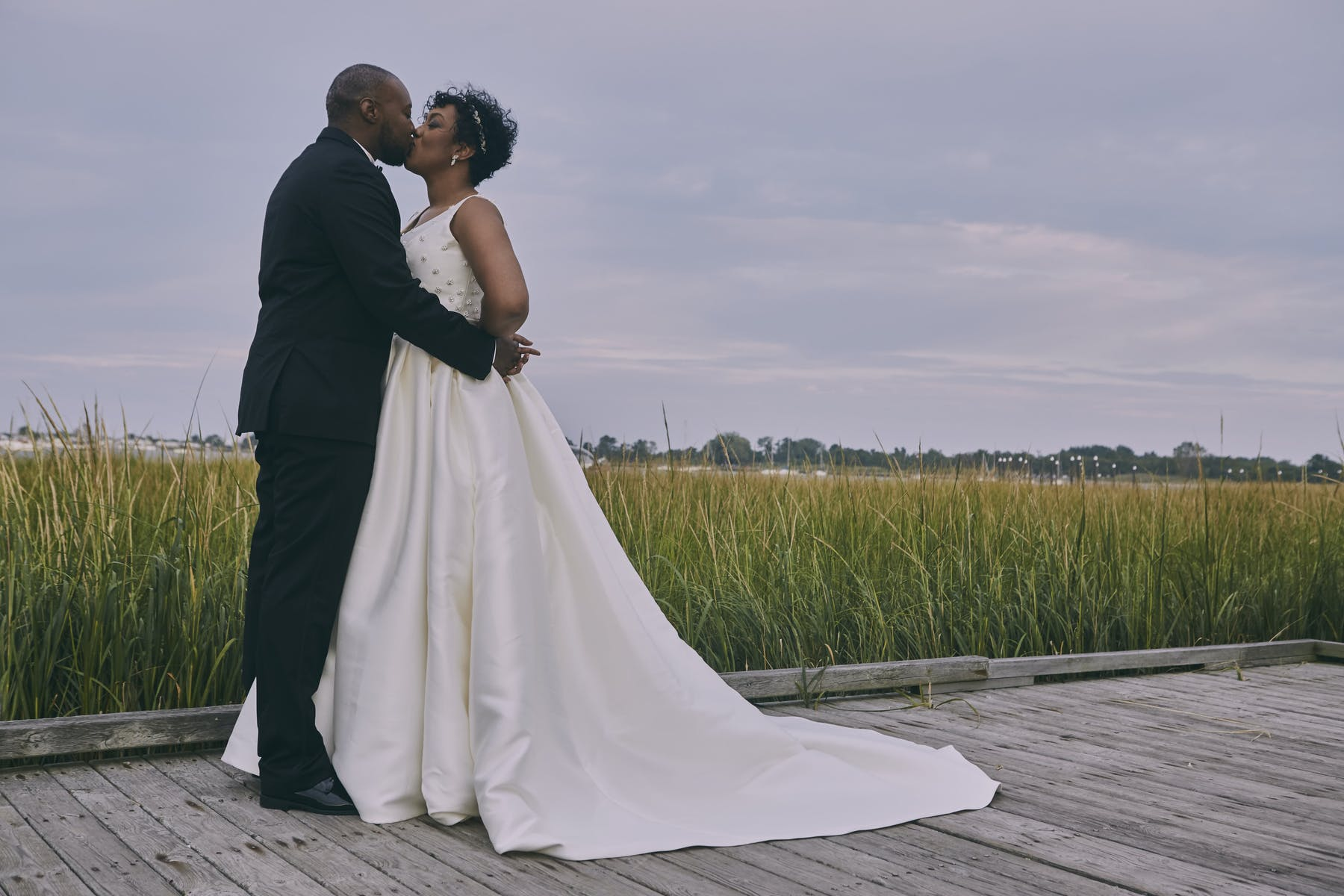 a couple kissing in front of a field
