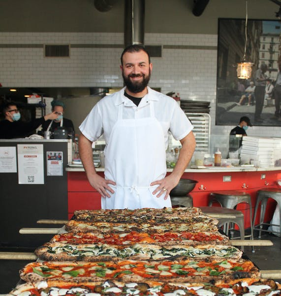 a man standing in front of a large pizza