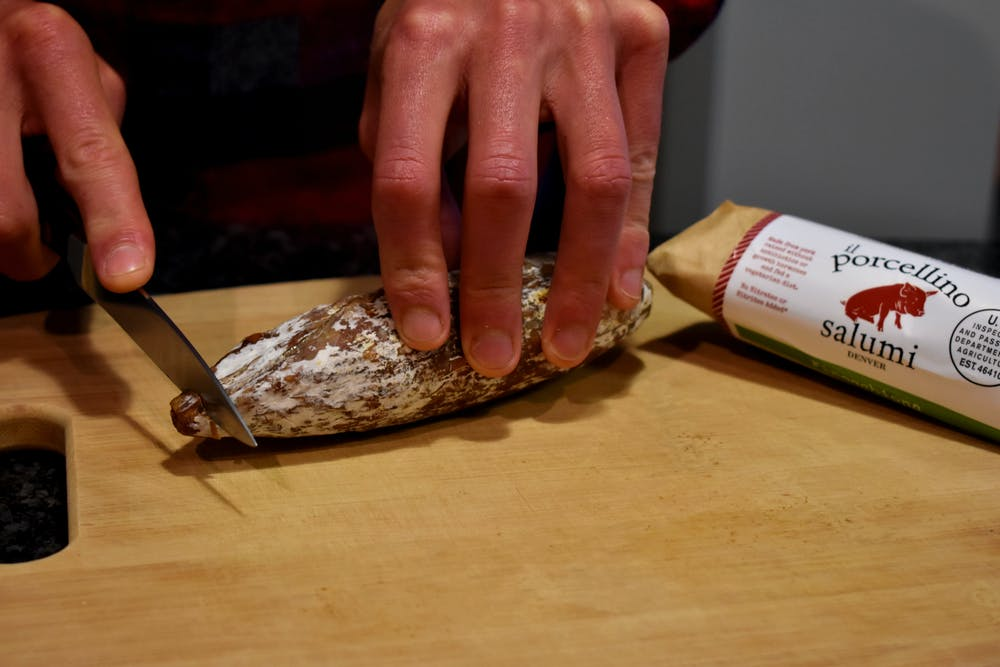 an image showing salami on a cutting board being held with the persons left hand as they cut the tip off the salami with their right hand
