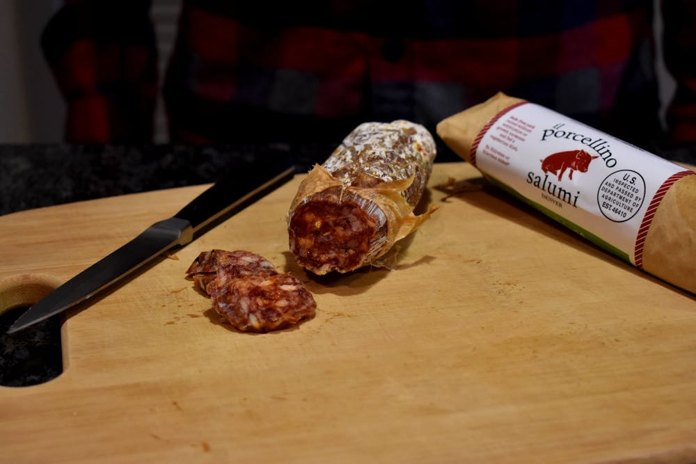 salami on a cutting board with it's casing pealed back and several bite size pieces cut off