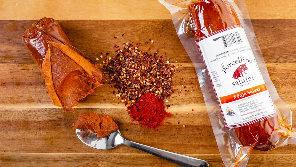 N'duja salami in it's packaging and out of it's packaging on a cutting board with a spoon cutting into the non-packaged N'duja with red spices next to them