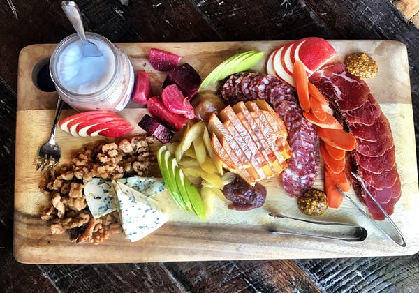 A fall harvest inspired charcuterie board shot from above. The board contains different cheese, cured meats, season fruits and veggies, and candied walnuts.