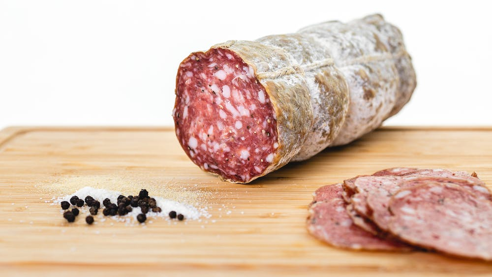 Large format genoa salami as a whole chub on a cutting board with genoa slices and spices in the foreground.